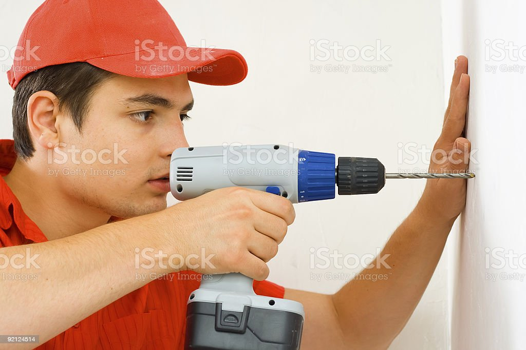 Man using a drilling machine to make a hole on the wall royalty-free stock photo