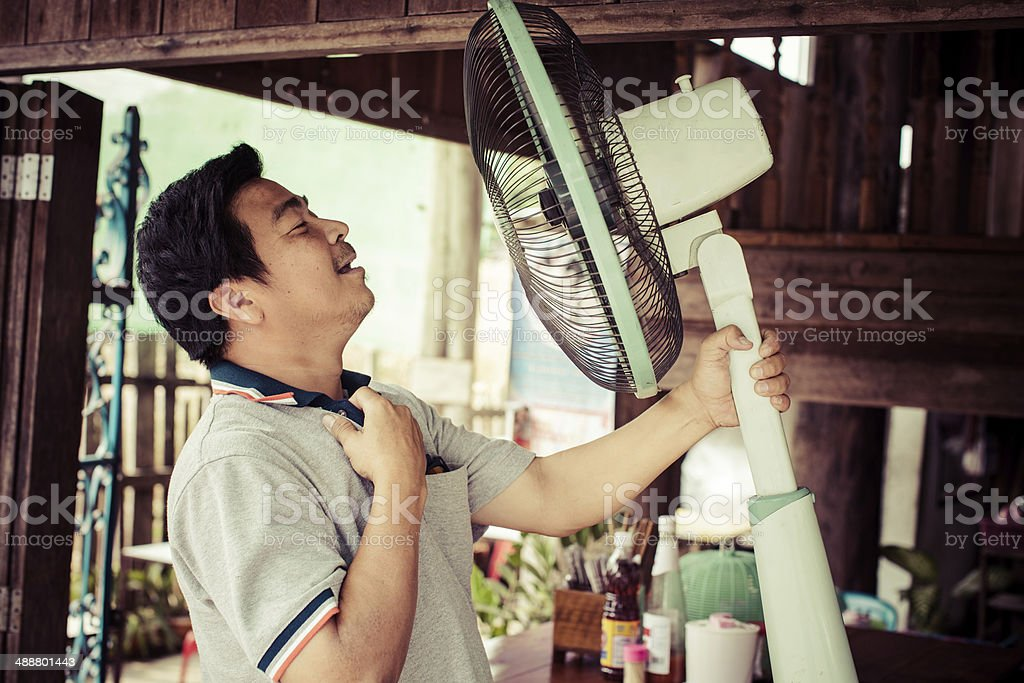 Man using a fan to cool off. stock photo