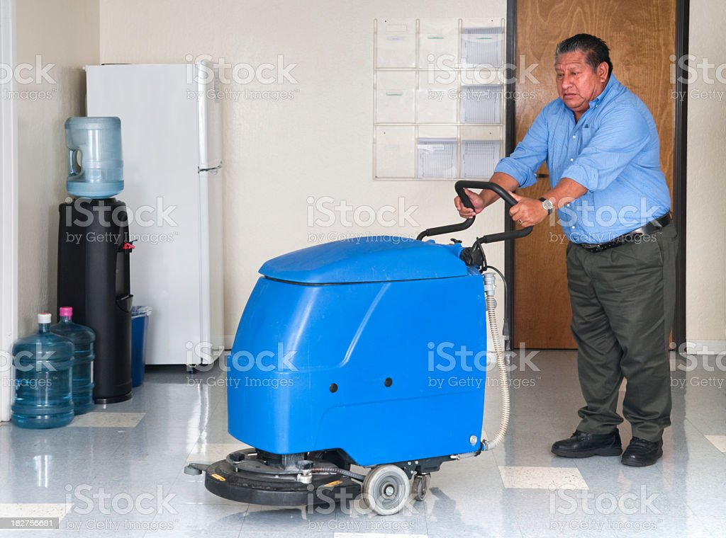 Man using a floor polishing machine in an office stock photo