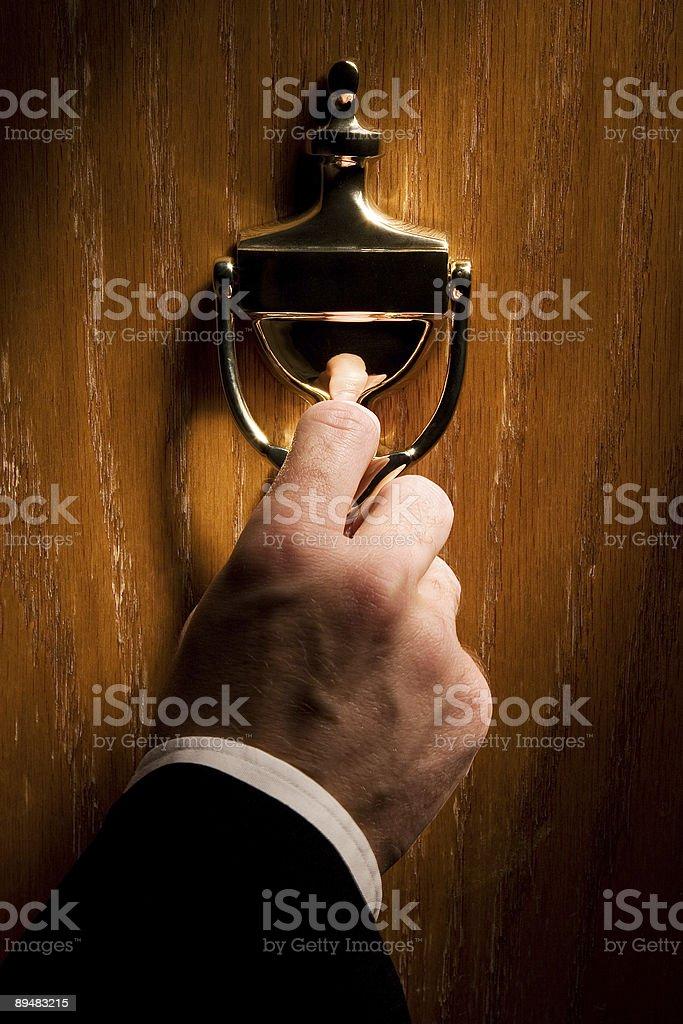 A man using a gold door knocker stock photo