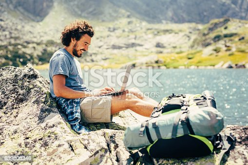 Male hiker resting and using a laptop on a rock near a lake in the mountain.