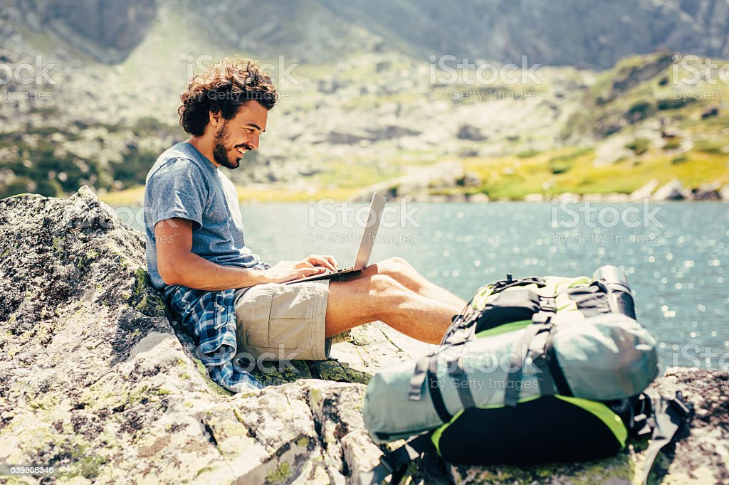 Man using a laptop in the mountain stock photo