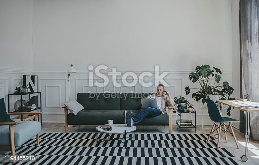 Handsome young Caucasian man using his laptop while sitting on a sofa in the modern office space.