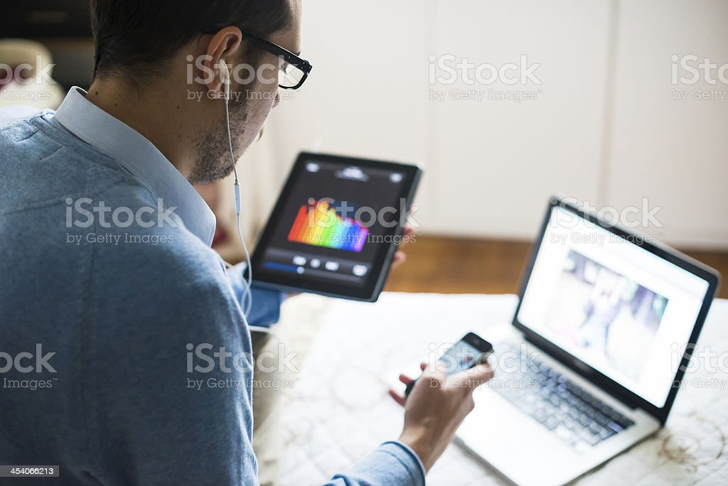 Man using a laptop, tablet, and cell phone at the same time stock photo