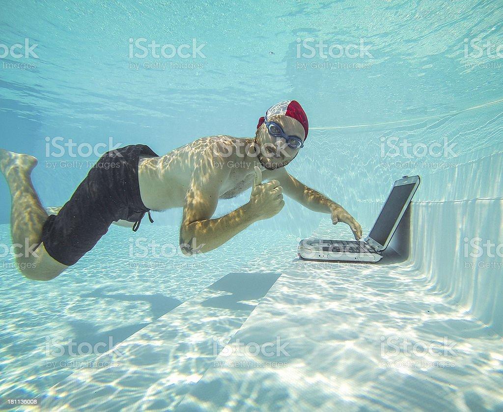 Man using a laptop underwater stock photo