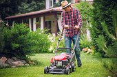 Man using a lawn mower in his back yard