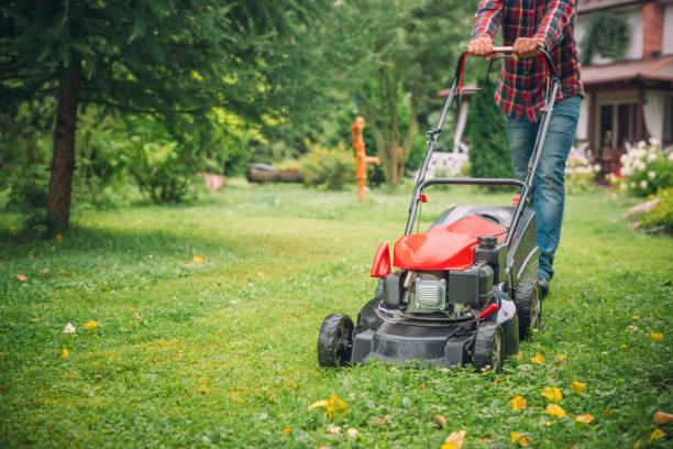 Mann mit einem Rasenmäher in seinem Hinterhof – Foto