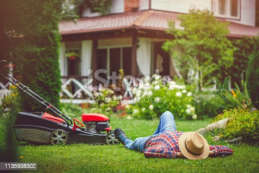 Man mowing grass near his house