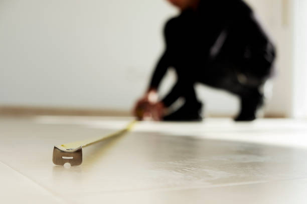 man using a measuring tape on a tiled floor stock photo
