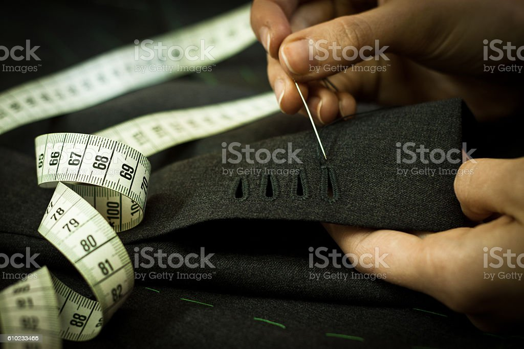 Man using a needle tp sew a jacket stock photo