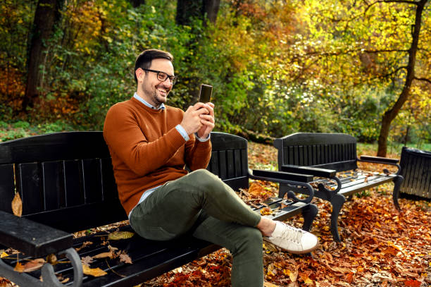 Man using a phone Smiling man sitting at park bench and using smartphone excitment stock pictures, royalty-free photos & images