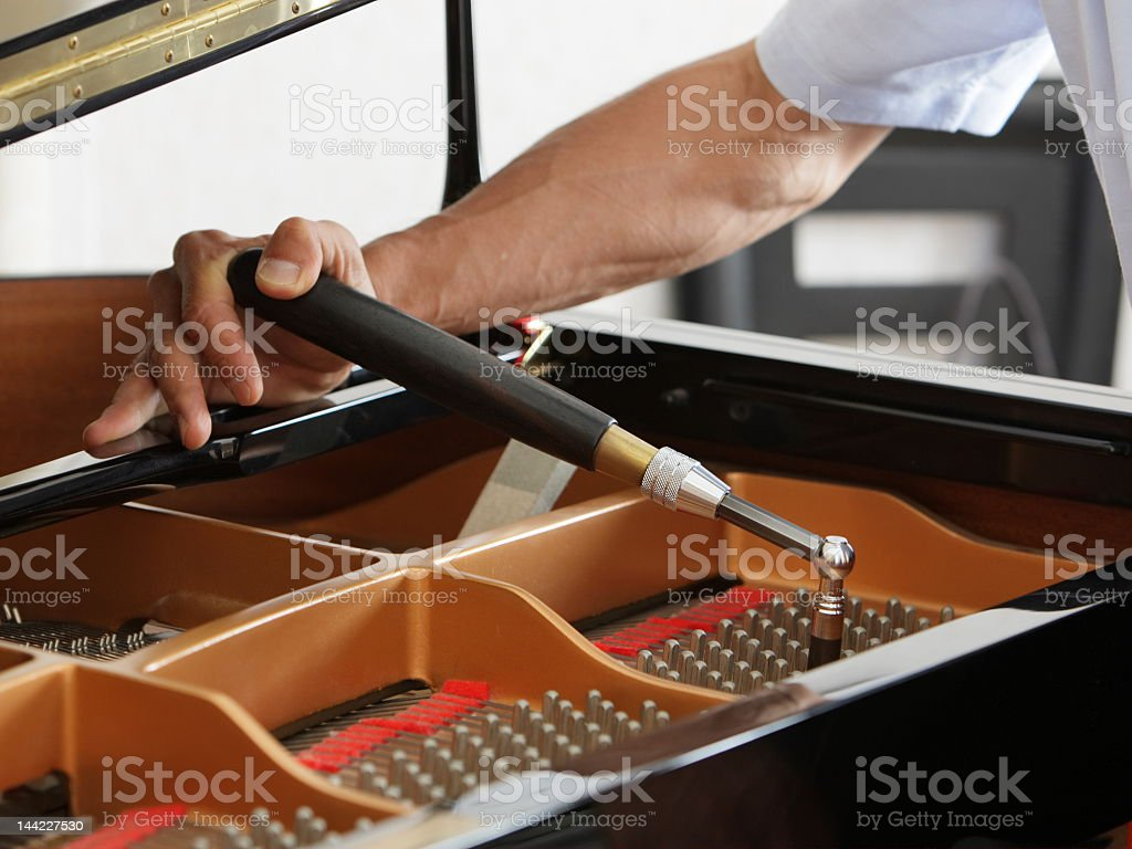 A man using a piano tuning tool to adjust a grand piano stock photo