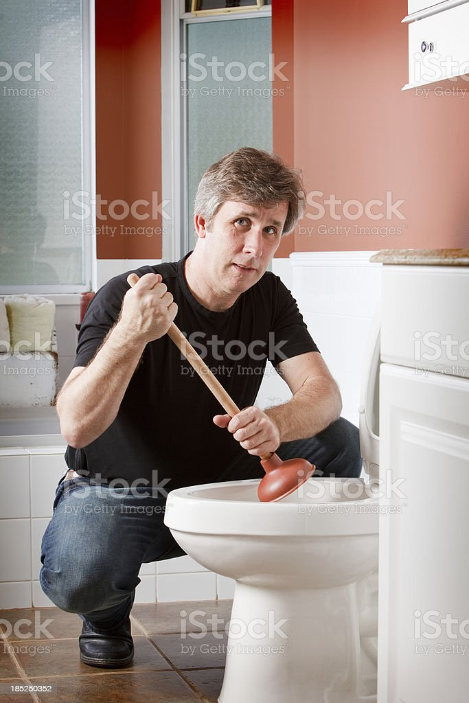 Man using a plunger to unplug the toilet royalty-free stock photo