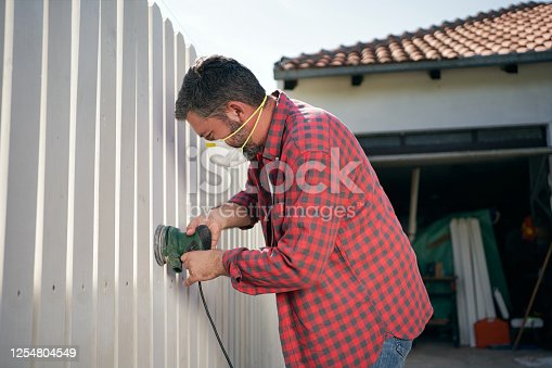 Adult man using a power tool to sand his home white wooden fence