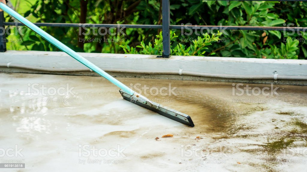 Man using a rubber floor squeegee for clean a balcony.