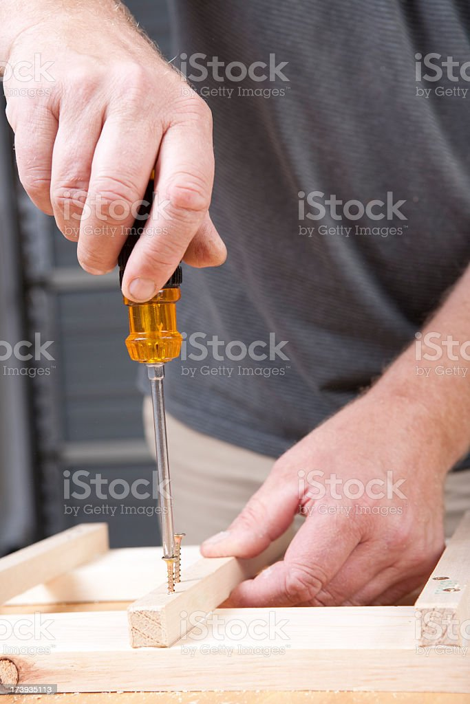 Man using a screwdriver to screw nails into pieces of wood stock photo