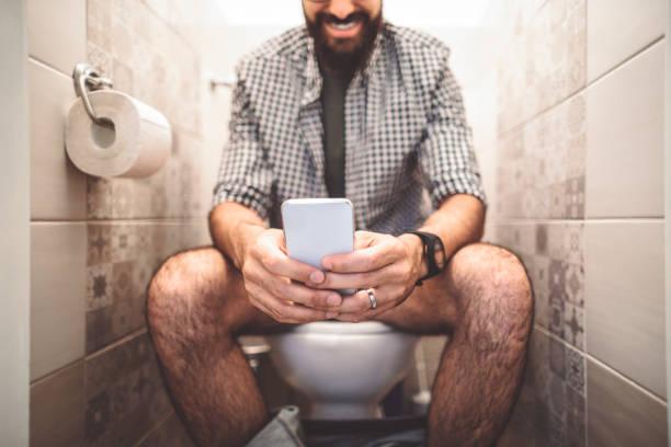 man met behulp van een slimme telefoon zittend op het toilet - cell phone toilet stockfoto's en -beelden