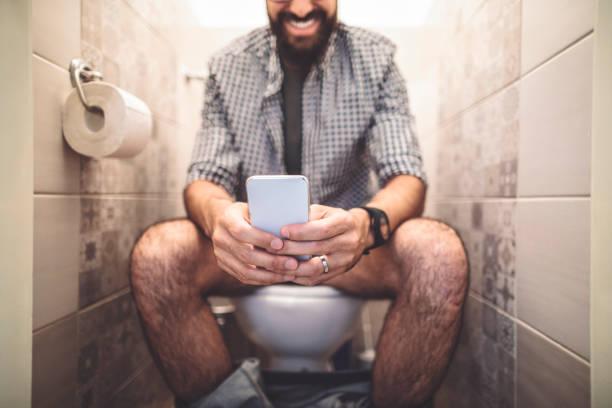 man die een smartphone gebruikt terwijl hij op het toilet zit - cell phone toilet stockfoto's en -beelden