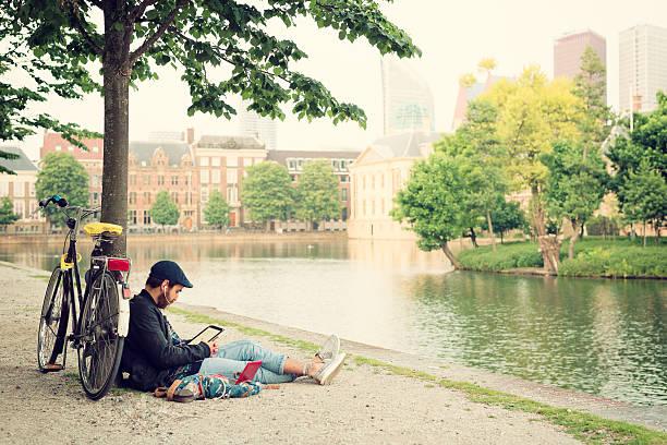 man using a tablet computer in the park. - den haag stockfoto's en -beelden
