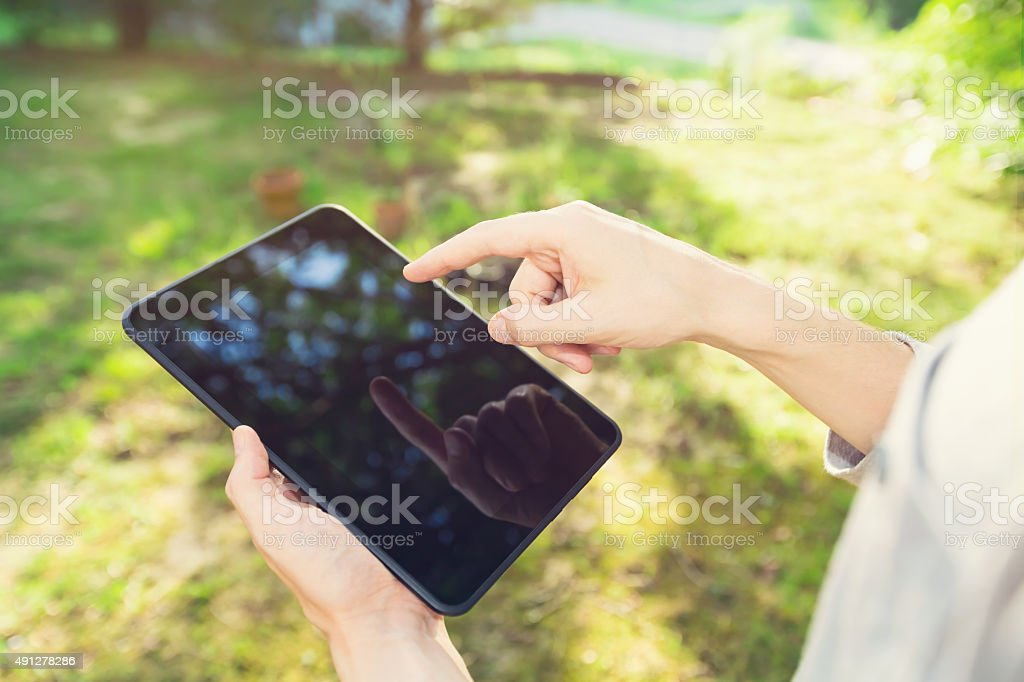 Man using a tablet computer outside stock photo