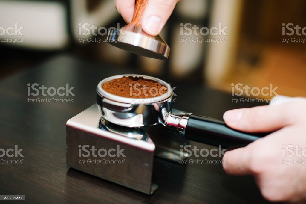 man using a tamper to press freshly ground coffee into a tablet royalty-free stock photo