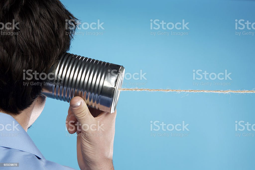 Man using a tin can telephone with blue background stock photo