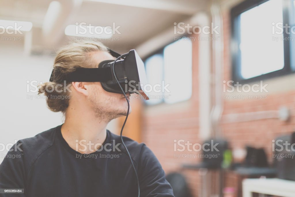 Man using a virtual reality headset in a new business office. Augmented reality zbiór zdjęć royalty-free