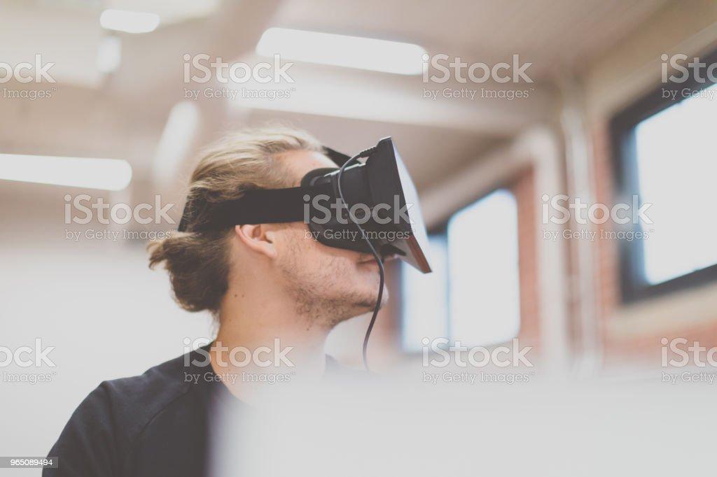 Man using a virtual reality headset in a start-up environment zbiór zdjęć royalty-free