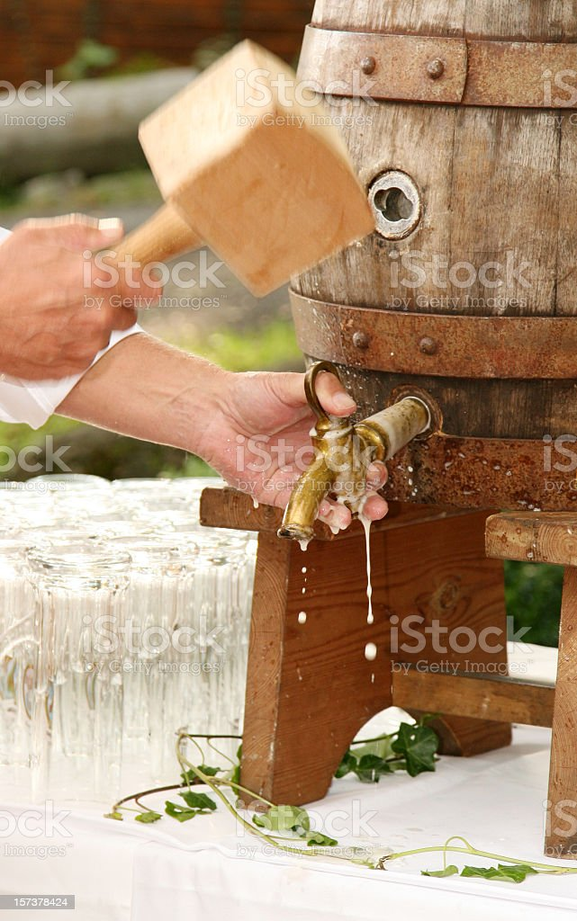 Man using a wooden mallet on a beer barrel stock photo