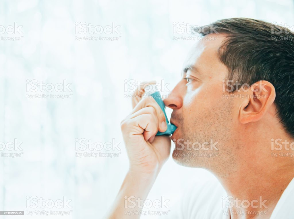 Man using an asthma inhaler stock photo