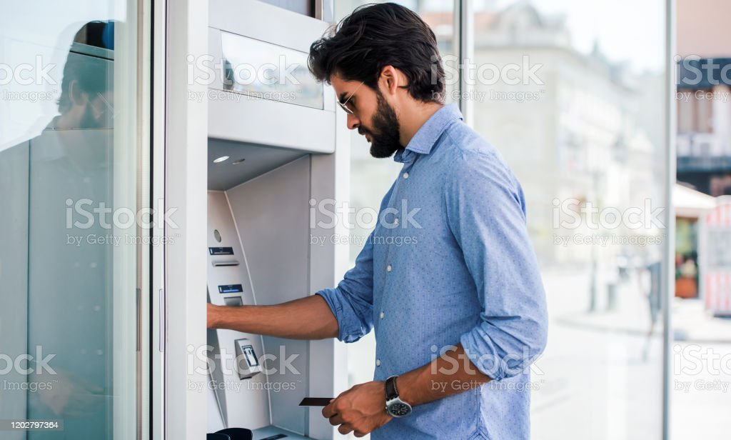 Man using an cash dispenser on the street Man using a street ATM machine and withdrawing money ATM Stock Photo