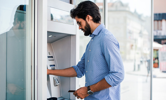 Man Using An Cash Dispenser On The Street Stock Photo - Download Image Now