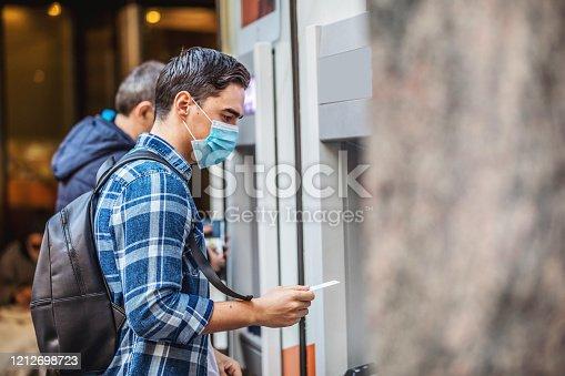 945598452 istock photo Man using an cash dispenser on the street 1212698723