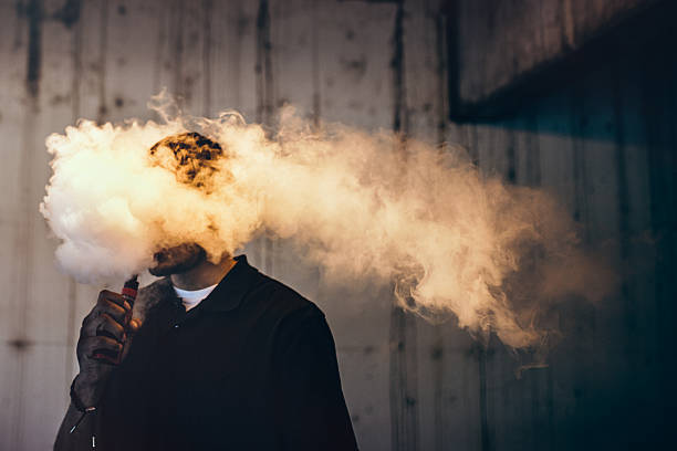 Man Using An Electric Cigarette A dark and high contrast image of a young adult male has a cloud of nicotine vapor