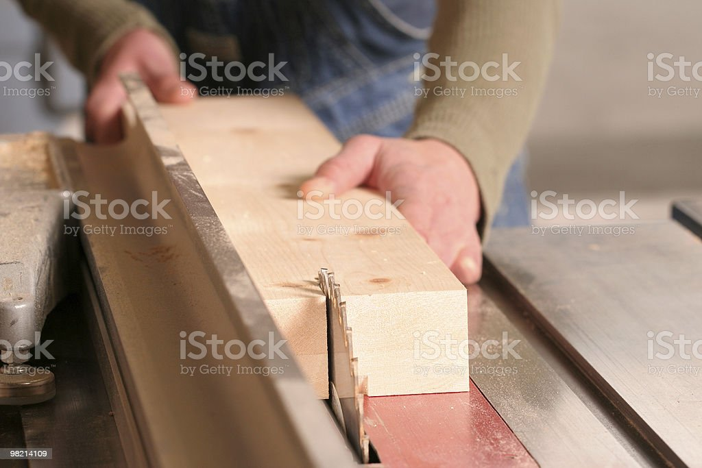 A man using an electric saw to chop wood royalty-free stock photo