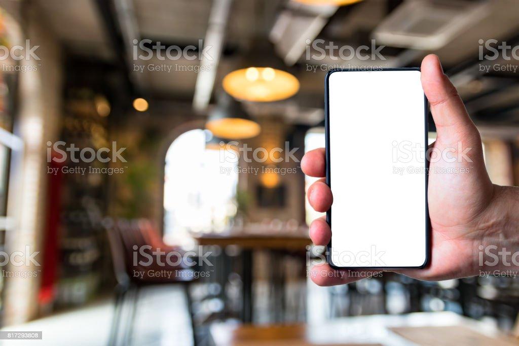 Man using bezel less smart phone in a restaurant. stock photo