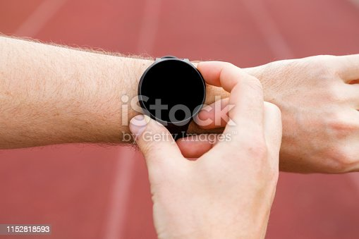 istock Man using black smart watch at stadium track. Checking heart rate before and after workout. Monitoring of daily health with device. Closeup. Place for text, logo or mobile app on empty screen. 1152818593