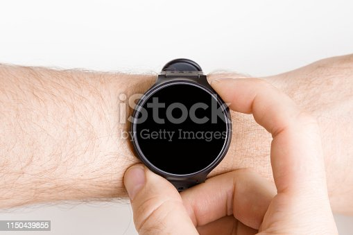istock Man using black smart watch on gray background. Fingers pushing buttons. Monitoring of daily health with modern device. Closeup. Point of view shot. Place for text, logo or mobile app on empty screen. 1150439855