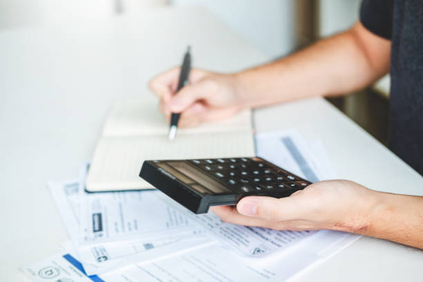 Man using calculator Accounting Calculating Cost Economic bills with money stack step growing growth saving money in home , finance concept stock photo