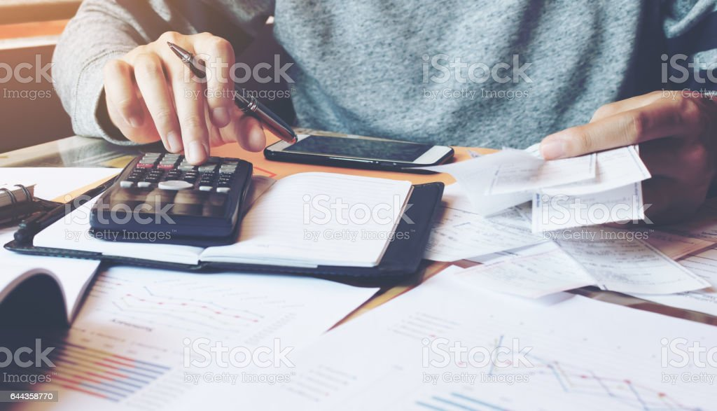Man using calculator and calculate bills in home office. stock photo