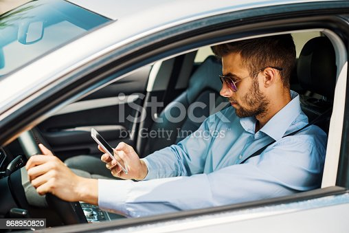 istock Man using car pooling service app on his smartphone 868950820