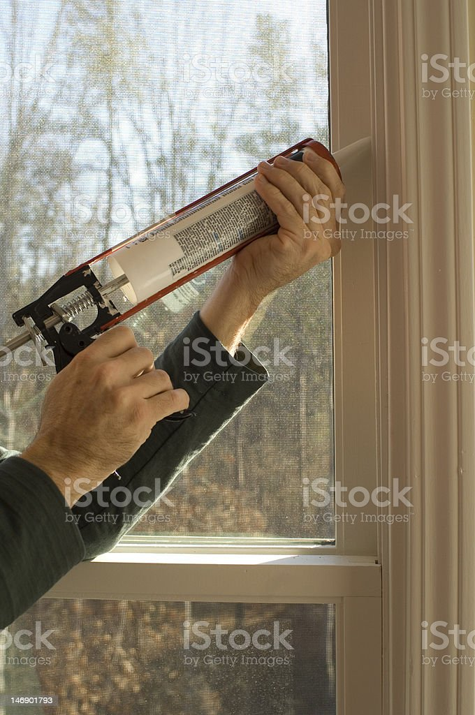 Man using caulking gun stock photo