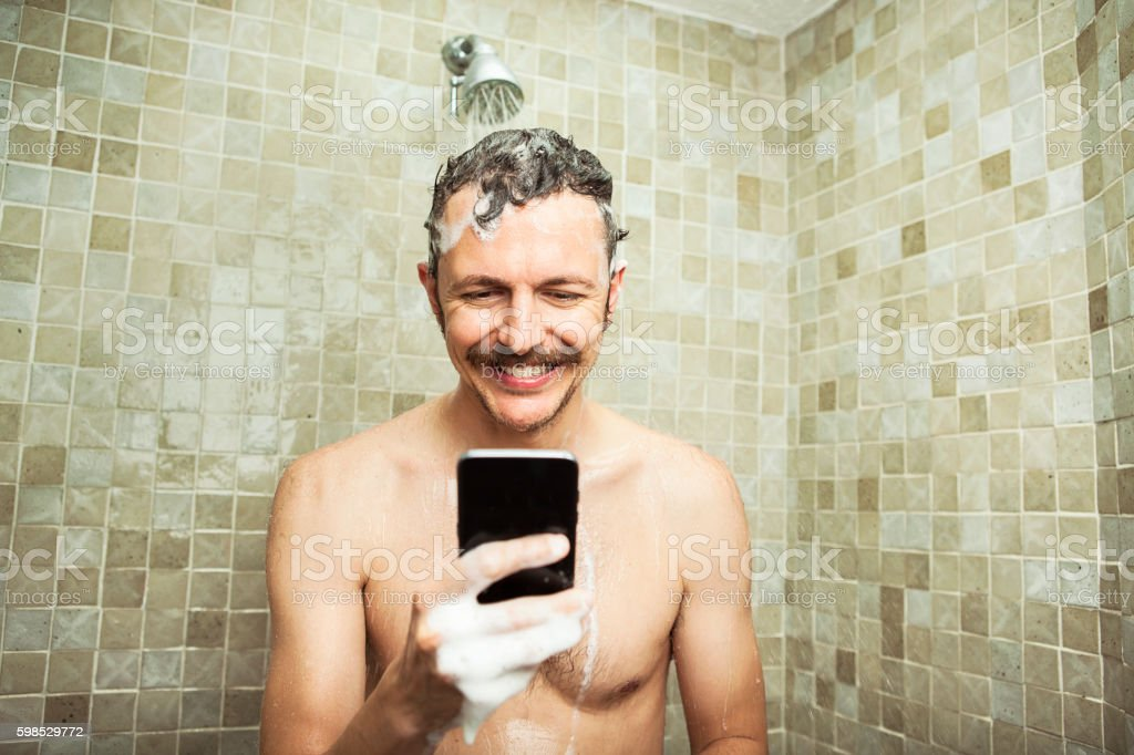Man using cell phone in the shower photo libre de droits