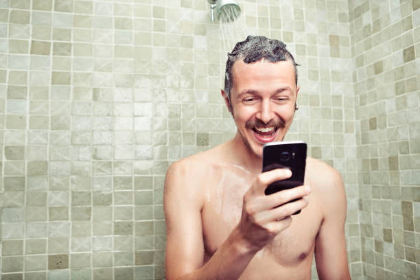 man using cell phone in the shower - smartphone addiction not groups stock pictures, royalty-free photos & images