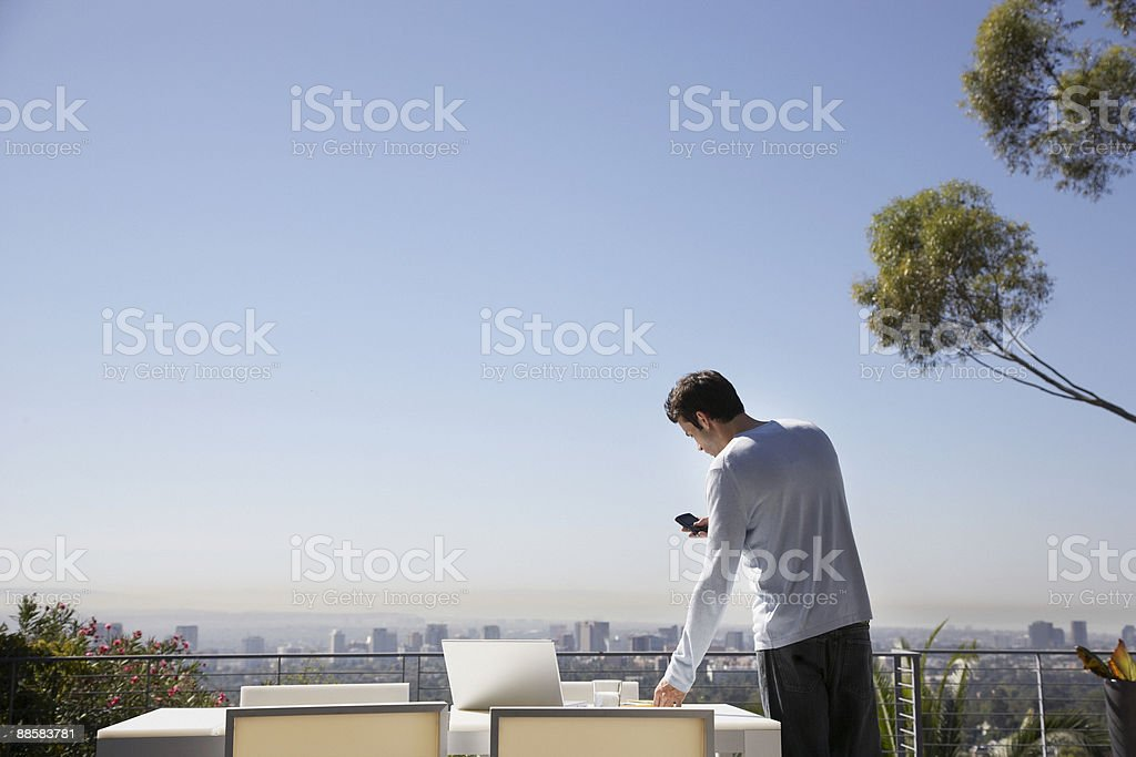 Man using cell phone on balcony royalty-free stock photo