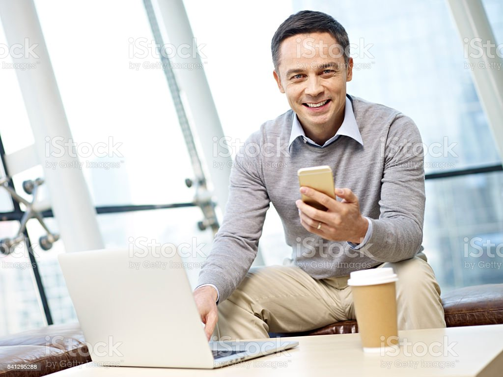 man using cellphone and laptop stock photo