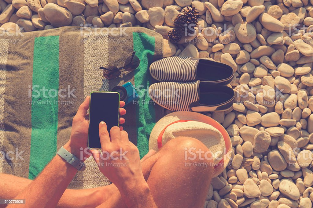 Man using cellphone on the beach. stock photo