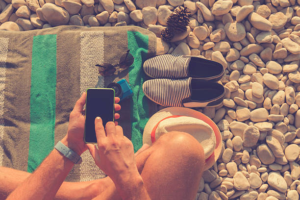 Man using cellphone on the beach. stock photo
