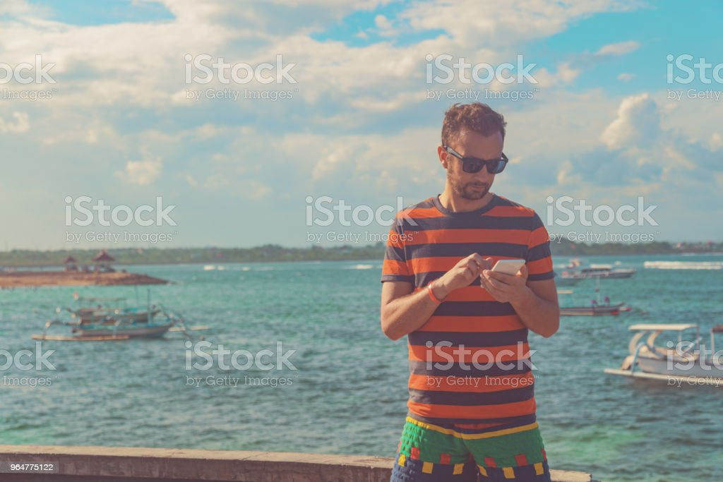 Man using cellphone on the ocean shore. royalty-free stock photo