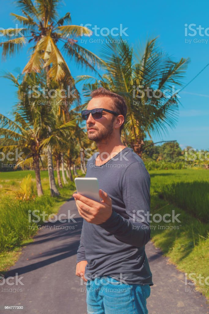 Man using cellphone / smartphone in tropical environment. royalty-free stock photo